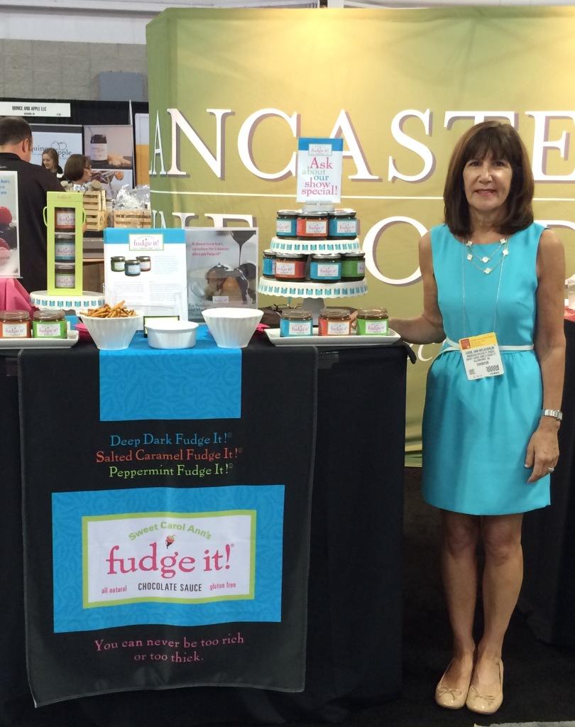 Carol Ann McLaughlin featuring her Sweet Carol Ann's Fudge It! sauce at a recent food show.